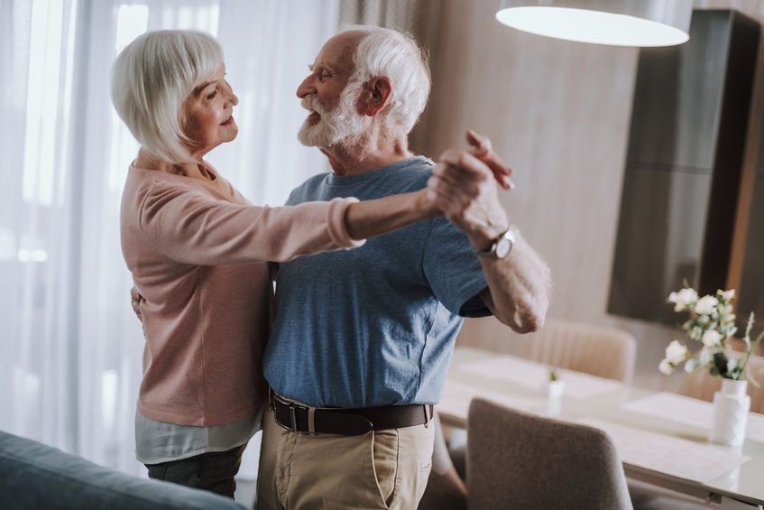 Joyful gray haired couple dancing in living room